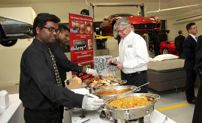 Anil Cherla and Matthew Sabu serving food to Michael Murphy