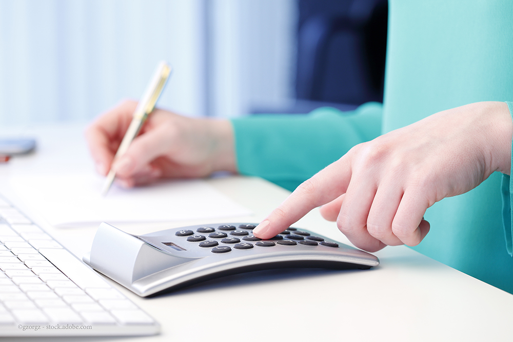 Close-up of female accountant making calculations while sitting at desk in office.