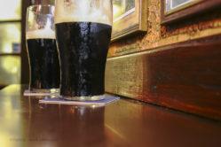 Two glasses of famous black Irish stout in Irish pub on wooden bar