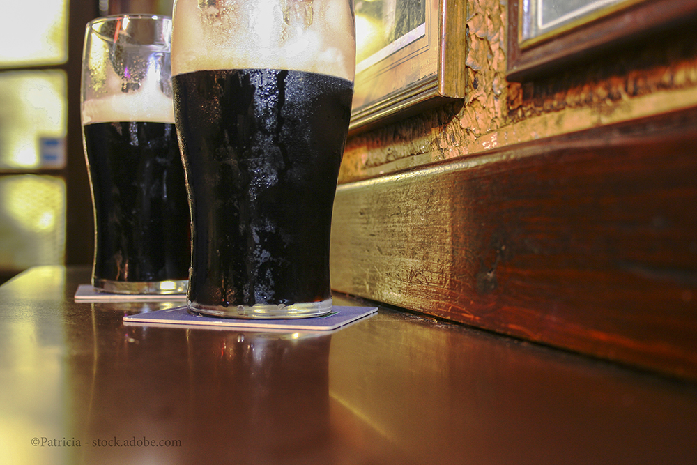 Two glasses of famous black Irish stout in Irish pub on wooden bar